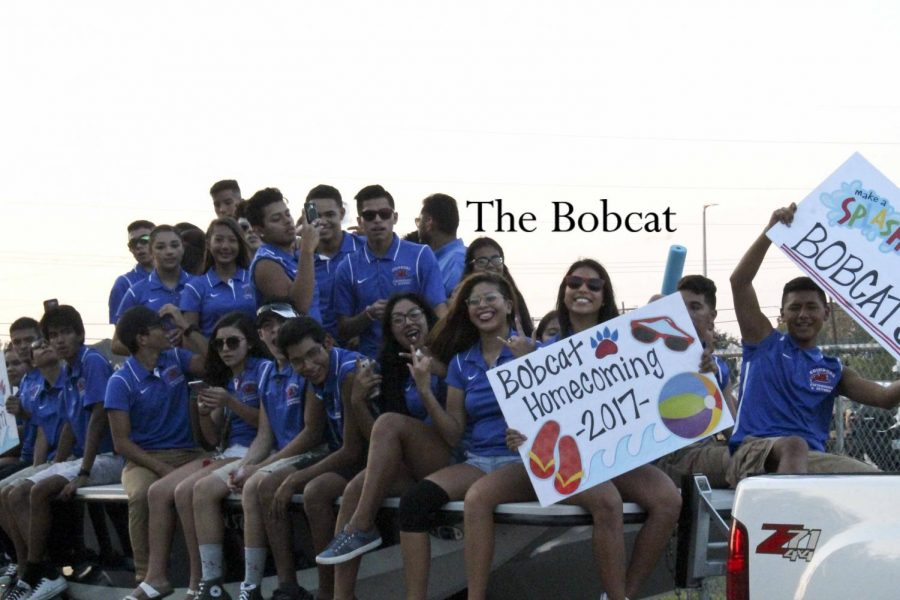 The swim team participates in the homecoming parade sporting shorts and sunglasses.
