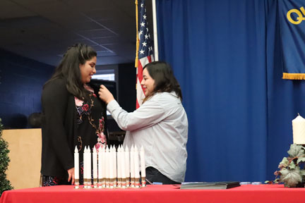 Guest Speaker Alexis Aguirre pins senior Bea Chavez at the Quill and Scroll induction ceremony.