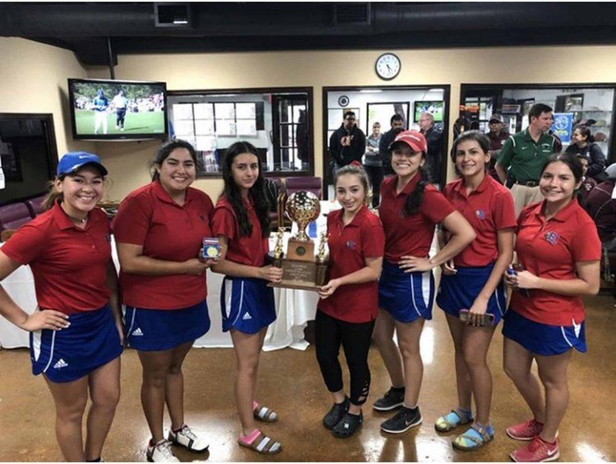 Sophomore Danelly Trevino, senior Beatriz Chavez, freshman Stephanie Trujillo, freshman Natalie Pena, senior Deborah Chavira, freshman Laura Lopez, and freshman Taylor Garcia pose with their First Place District trophy.