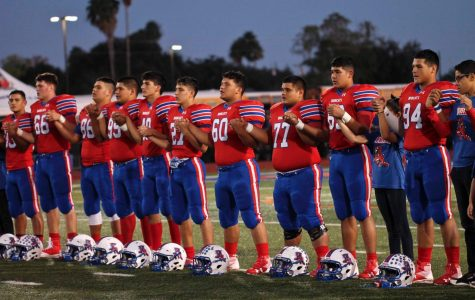 Football team stands together for the National Anthem before their last home game of the regular season.