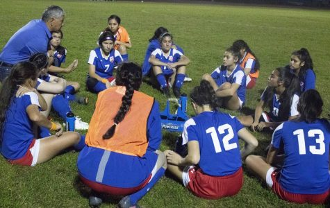 The Varsity Girls Soccer team listens to some words of advice from their coach.
