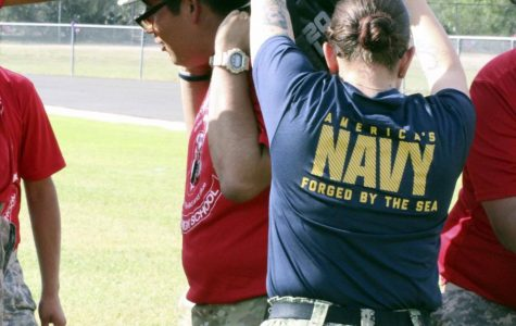 US Navy Sailor helps the JROTC cadets with their obstacle during the Mini Bootcamp.