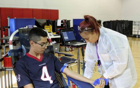 Senior Christian Cano donates blood during the blood drive hosted at school.
