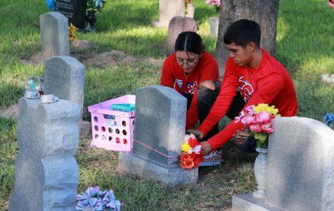 Junior Briana Lazo and Senior Demitri Galindo decorate a child's tombstone in celebration of 'Dia de los Muertos.'