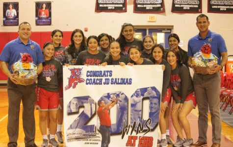 Girls Basketball Coach, JD Salinas stands with his team after being awarded for his 200th win.