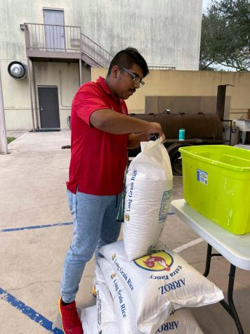 Josue Alvarez begins to prepare food bags for people in the community. First Baptist Church hosts