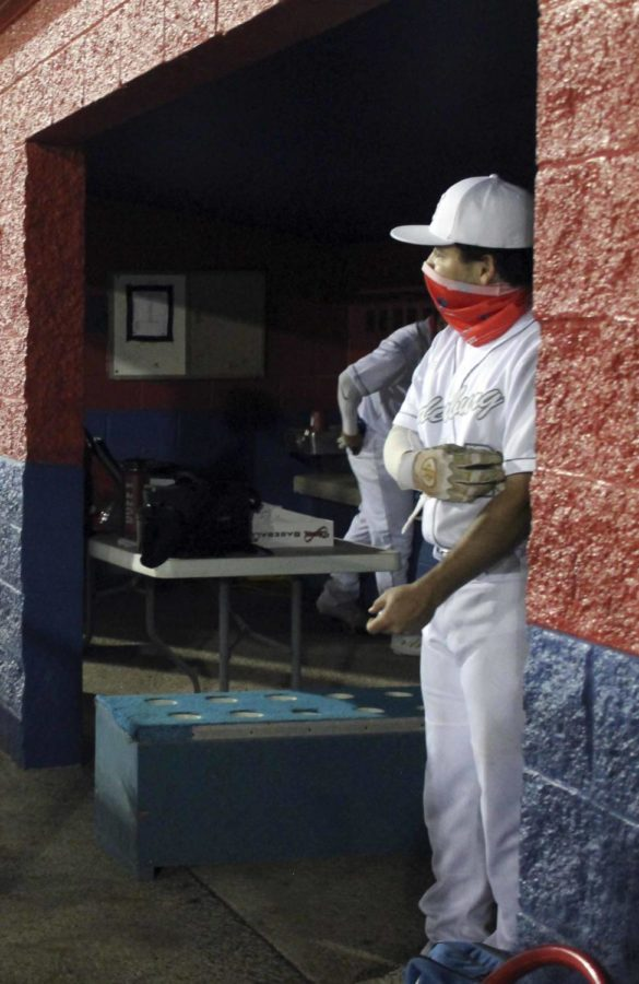 Adan Adame stands in the dugout following Covid safety protocol.